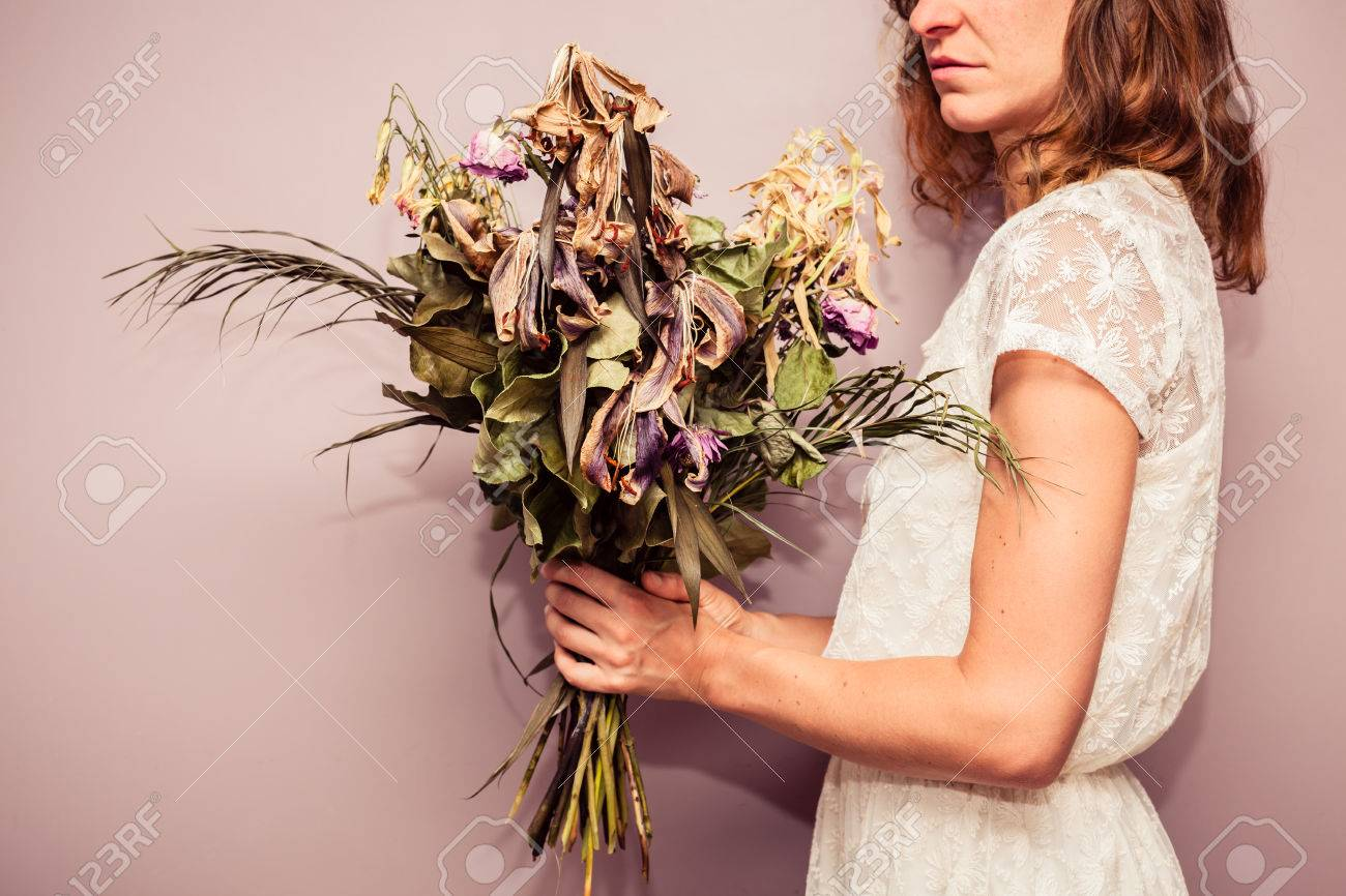 A Young Woman Is Holding A Bouquet Of Dead Flowers Stock Photo ...