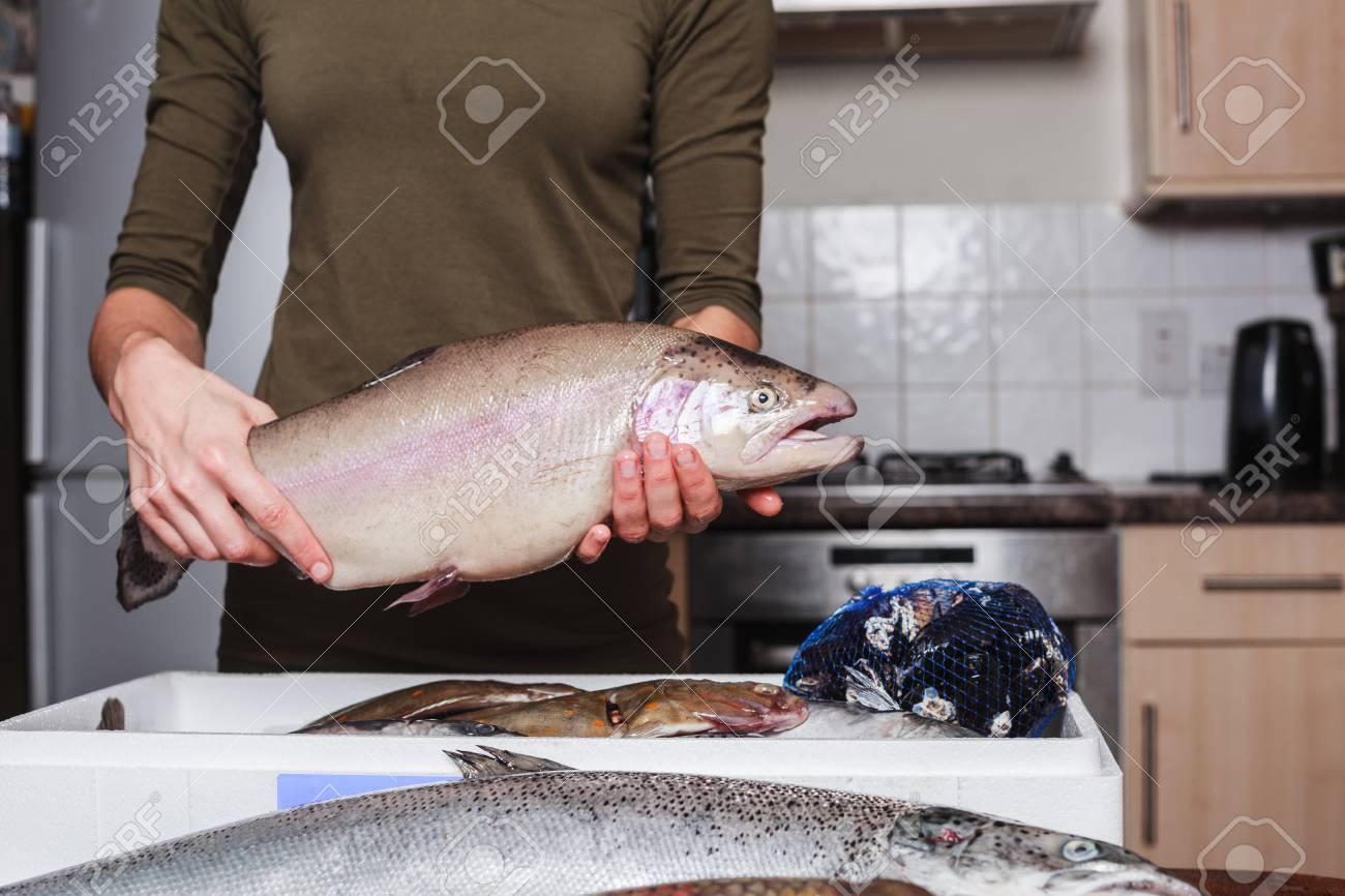 Eine Junge Frau Ist In Ihrer Küche Mit Einem Kasten Von Fisch Und ...