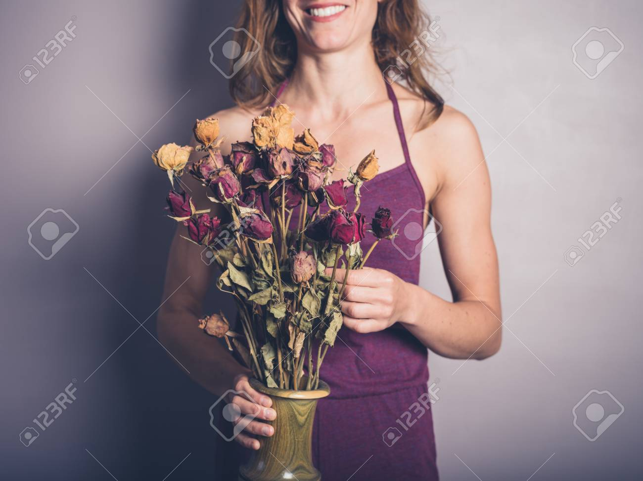A Young Woman Is Standing With A Bouquet Of Dead Flowers Stock Photo