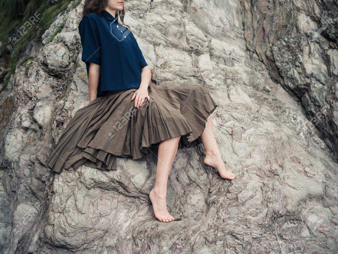2b421d1d4 Una mujer descalza hermosa joven que llevaba una falda está sentado sobre  unas rocas