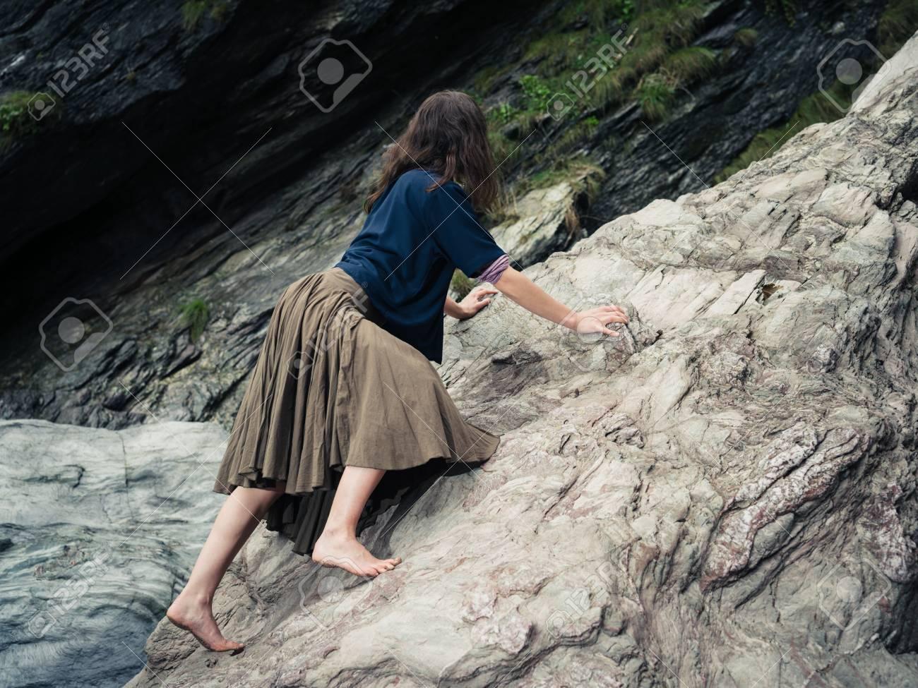 e82712f02 Una mujer descalza joven weaing una falda está subiendo una roca