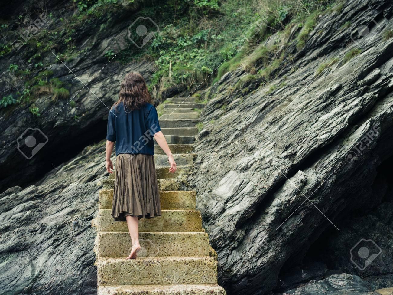 fbdc5a0f3 Una mujer descalza joven está caminando en unas escaleras que conducen un  acantilado