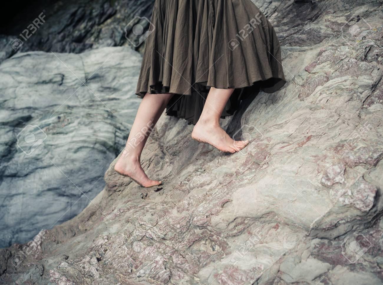 872ceef73 Los pies descalzos de una mujer joven mientras ella está subiendo por una  superficie de roca