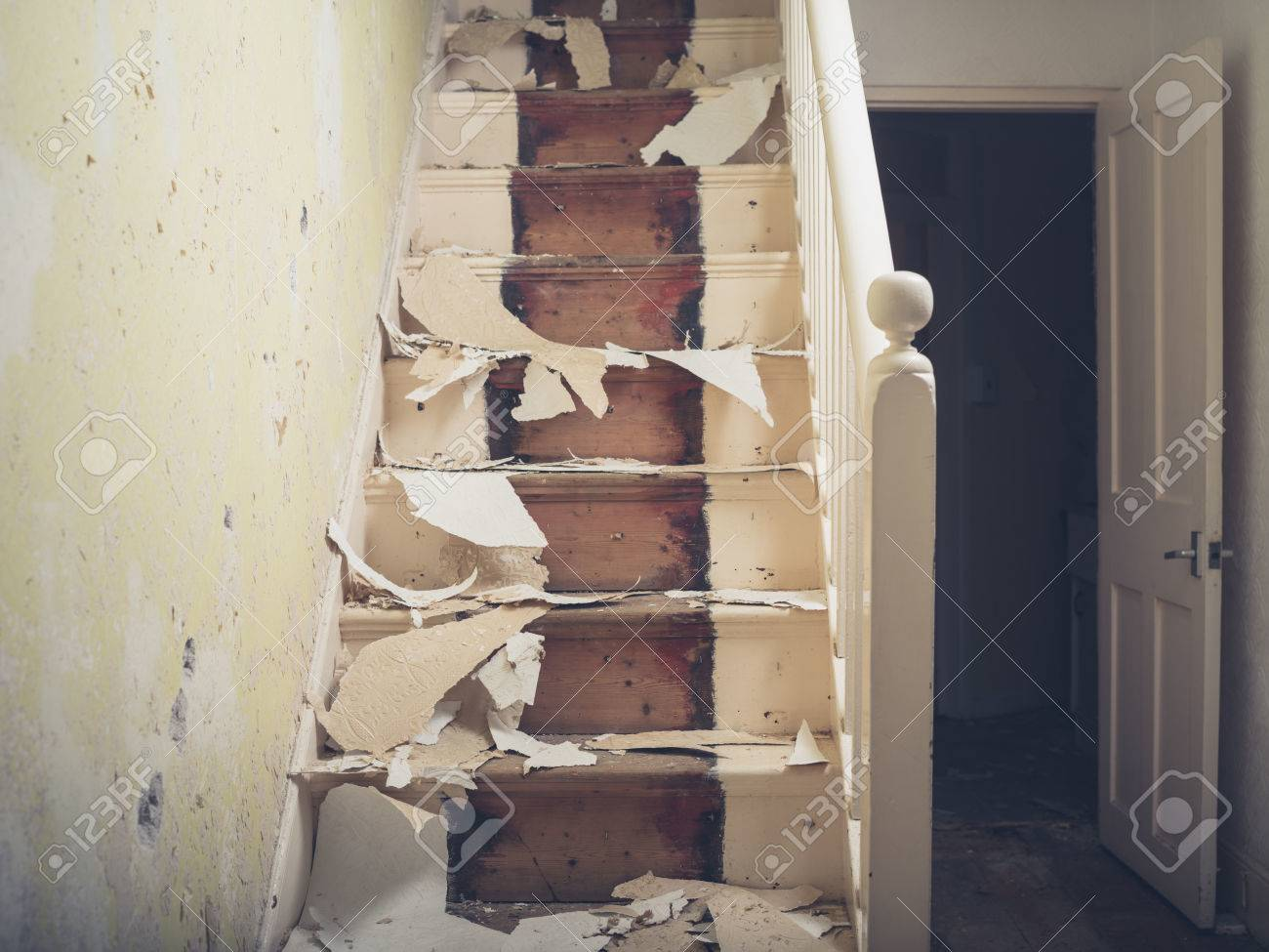 Een oude trap in een victoriaans huis met stukjes behang en