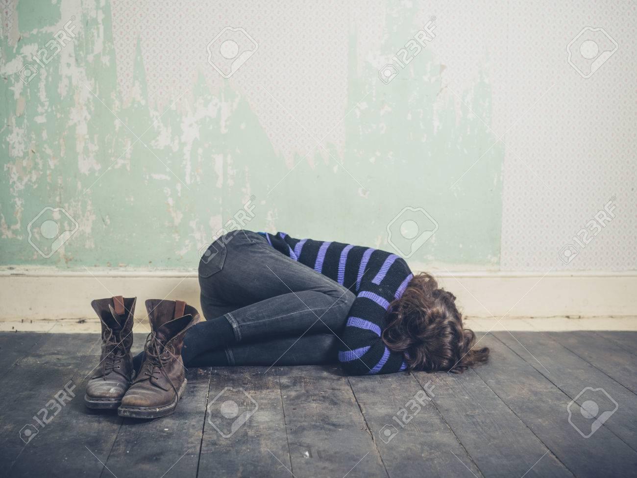 Una giovane donna triste è sdraiata sul pavimento in una stanza vuota con un paio di stivali in primo piano