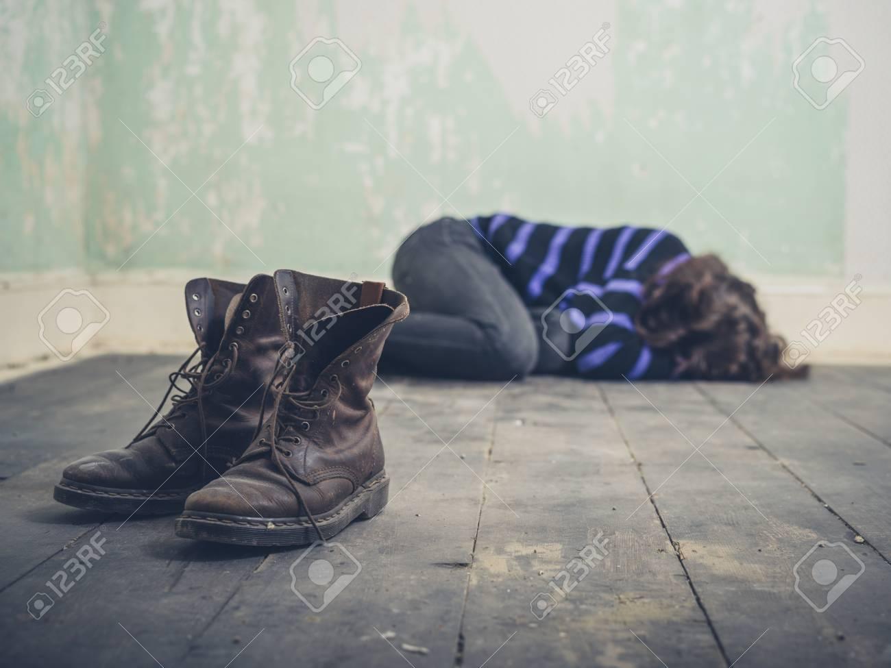 Una giovane donna triste è sdraiato sul pavimento in una stanza vuota con un paio di stivali in primo piano