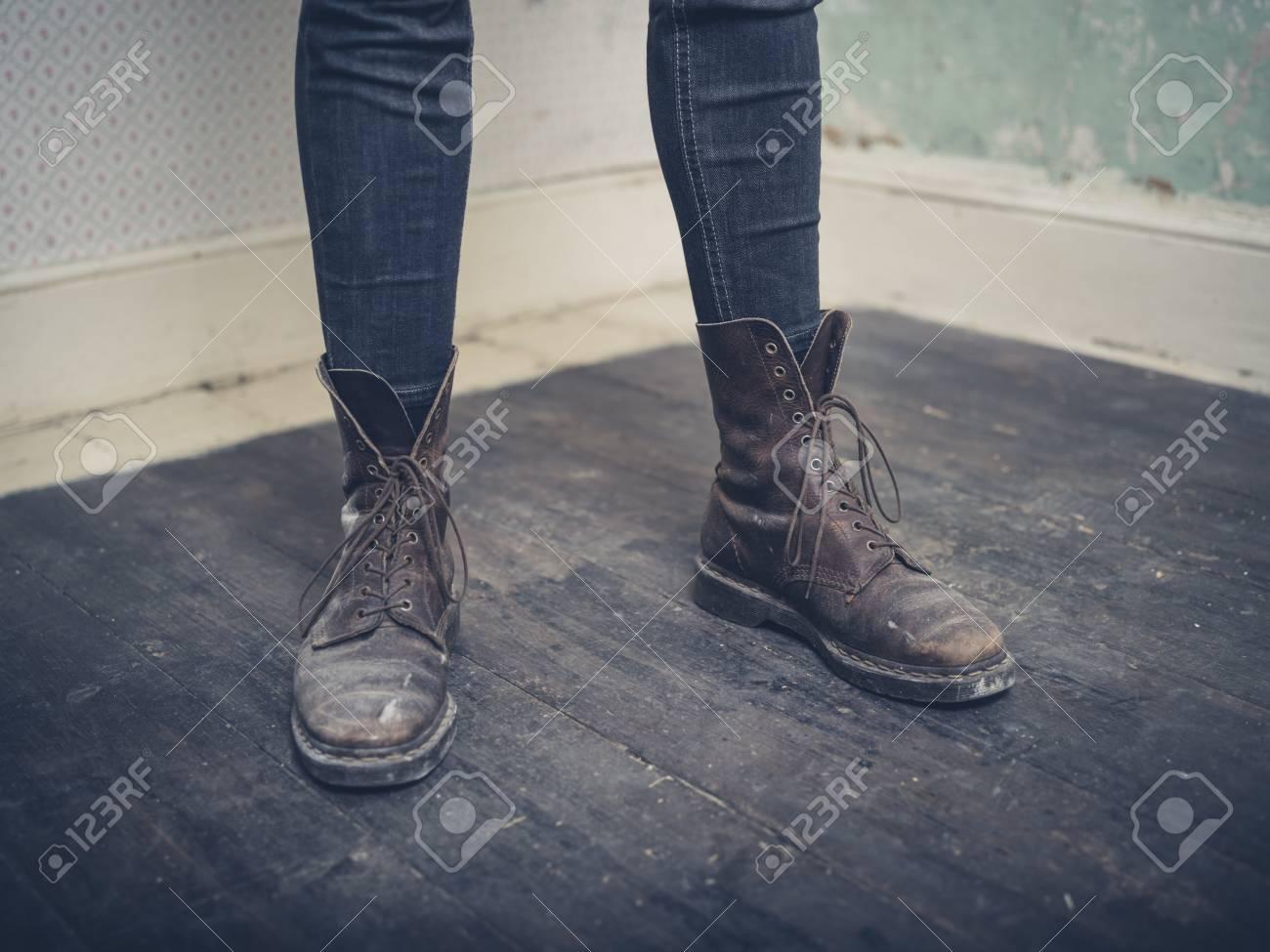 Un giovane persona che indossa stivali di pelle è in piedi in una stanza vuota