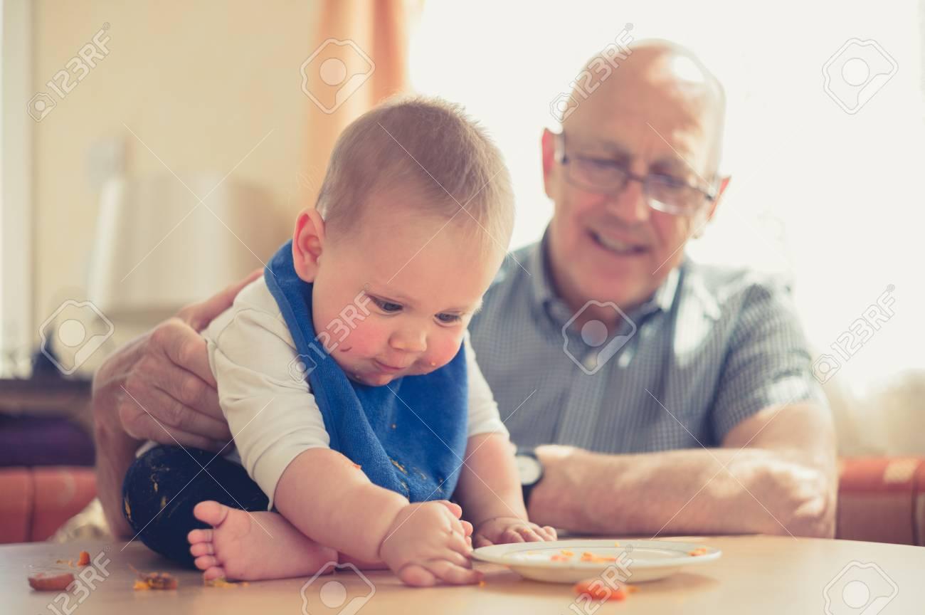 Immagini Stock Un Nonno E Seduto A Un Tavolo E Sta Aiutando Il Nipote Del Suo Bambino A Imparare A Mangiare I Solidi Image 81605655