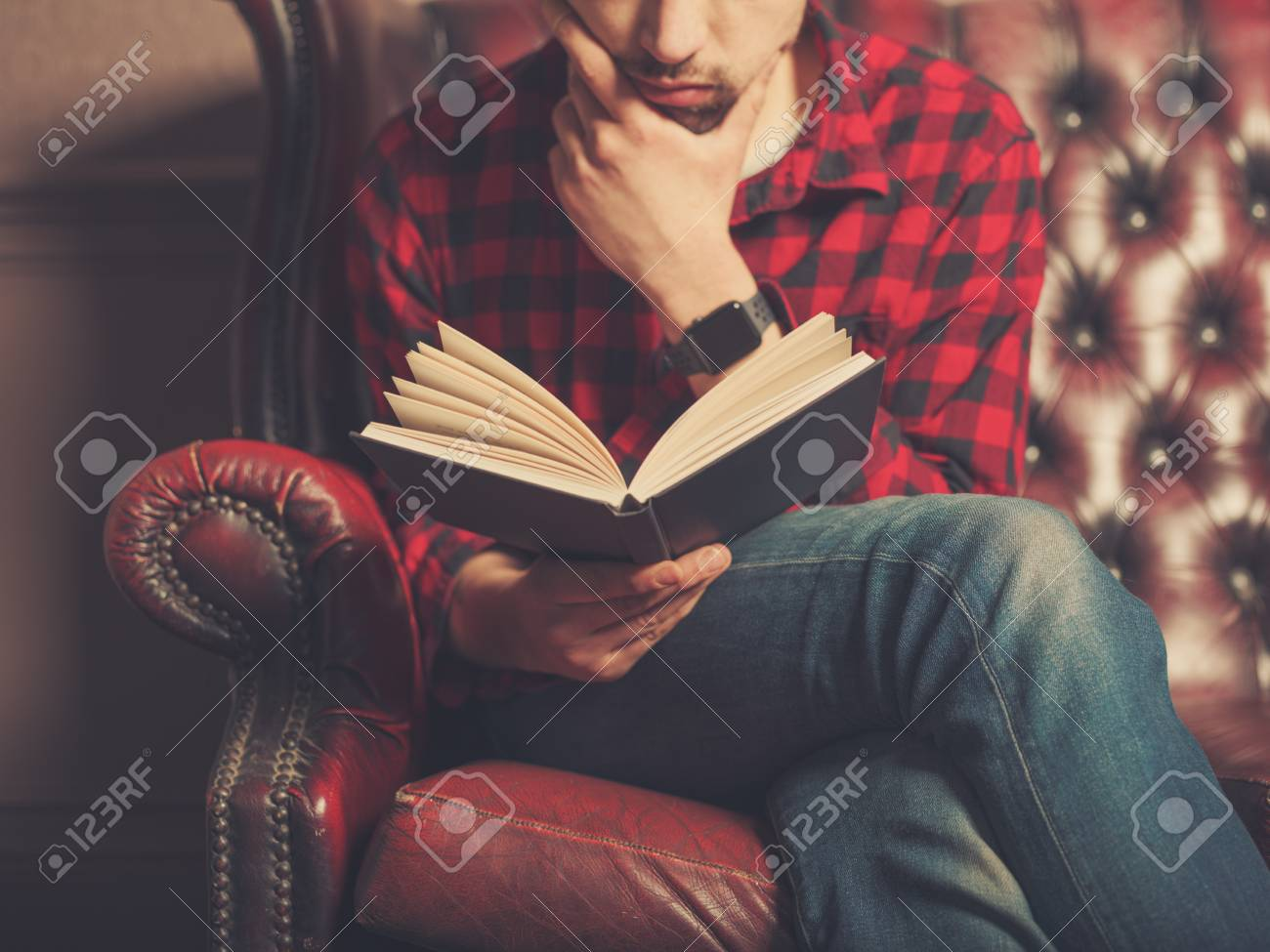A Young Man Sitting On A Leather Sofa Is Reading A Book
