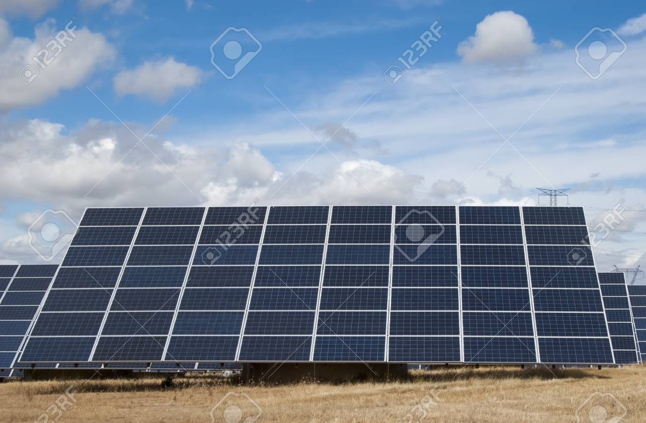 Modern solar panels harvesting clean solar energy under the sun, in a beautiful dry field Stock Photo - 21580014