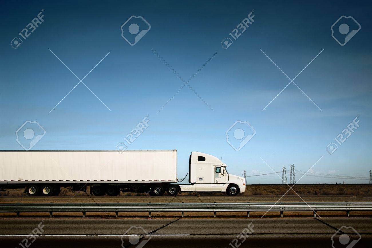 White freight truck driving on freeway under blue sky. Stock Photo - 4238083