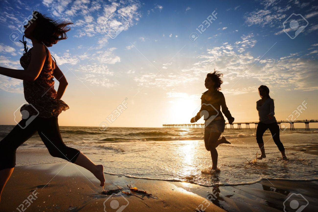 Three girls at the beach running by the ocean at sunset Stock Photo - 4215297