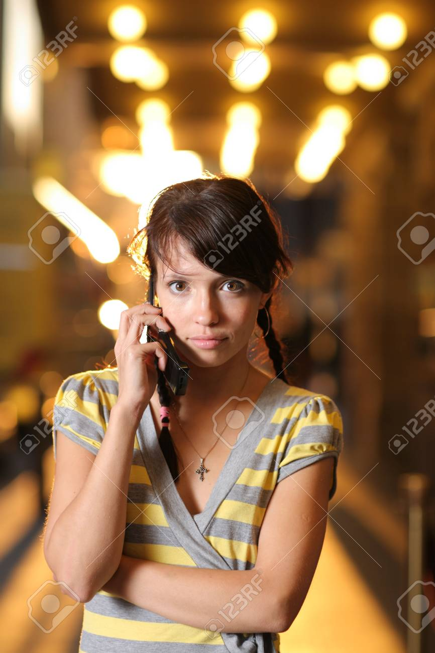 Cute teenage girl with cell phone on brightly lit street Stock Photo - 4664953