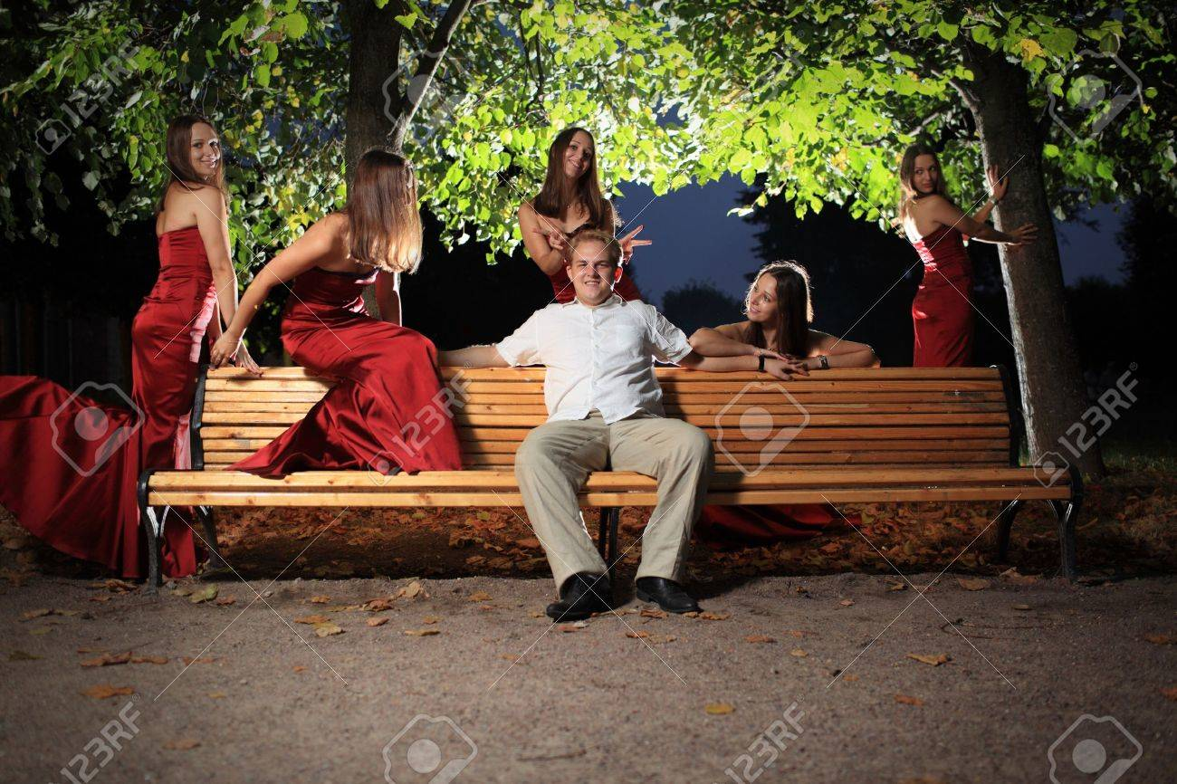 Happy young man on bench in night park, surrounded by sexy woman in red dress. Stock Photo - 7622247
