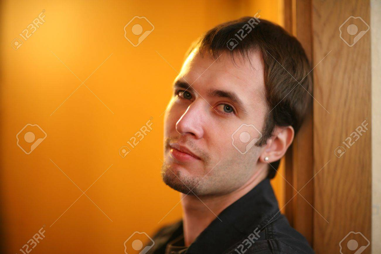 Portrait of handsome young adult man leaning on door frame, looking at camera. Stock Photo - 7660791