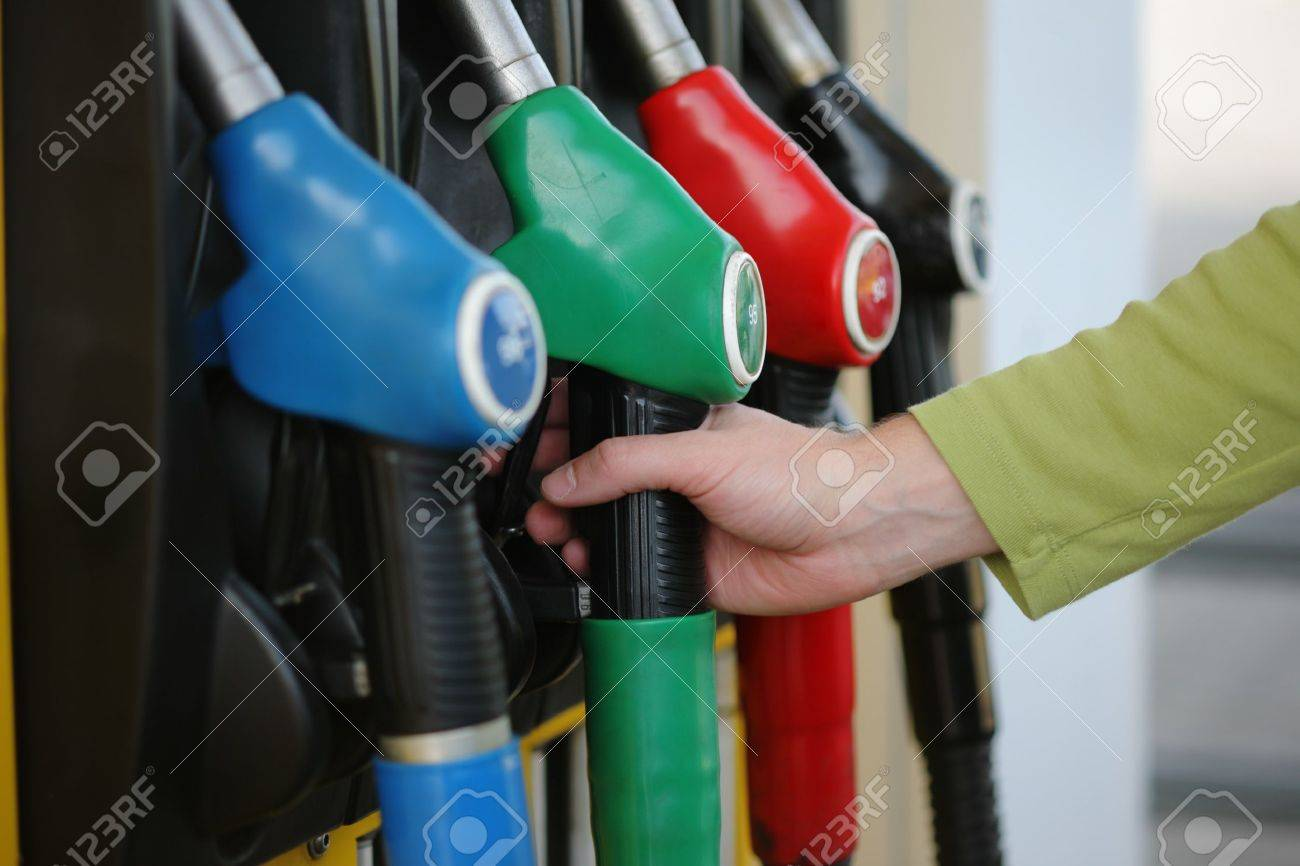 Closeup of male hand holding gas pump nozzle at gas station. Stock Photo - 7784915