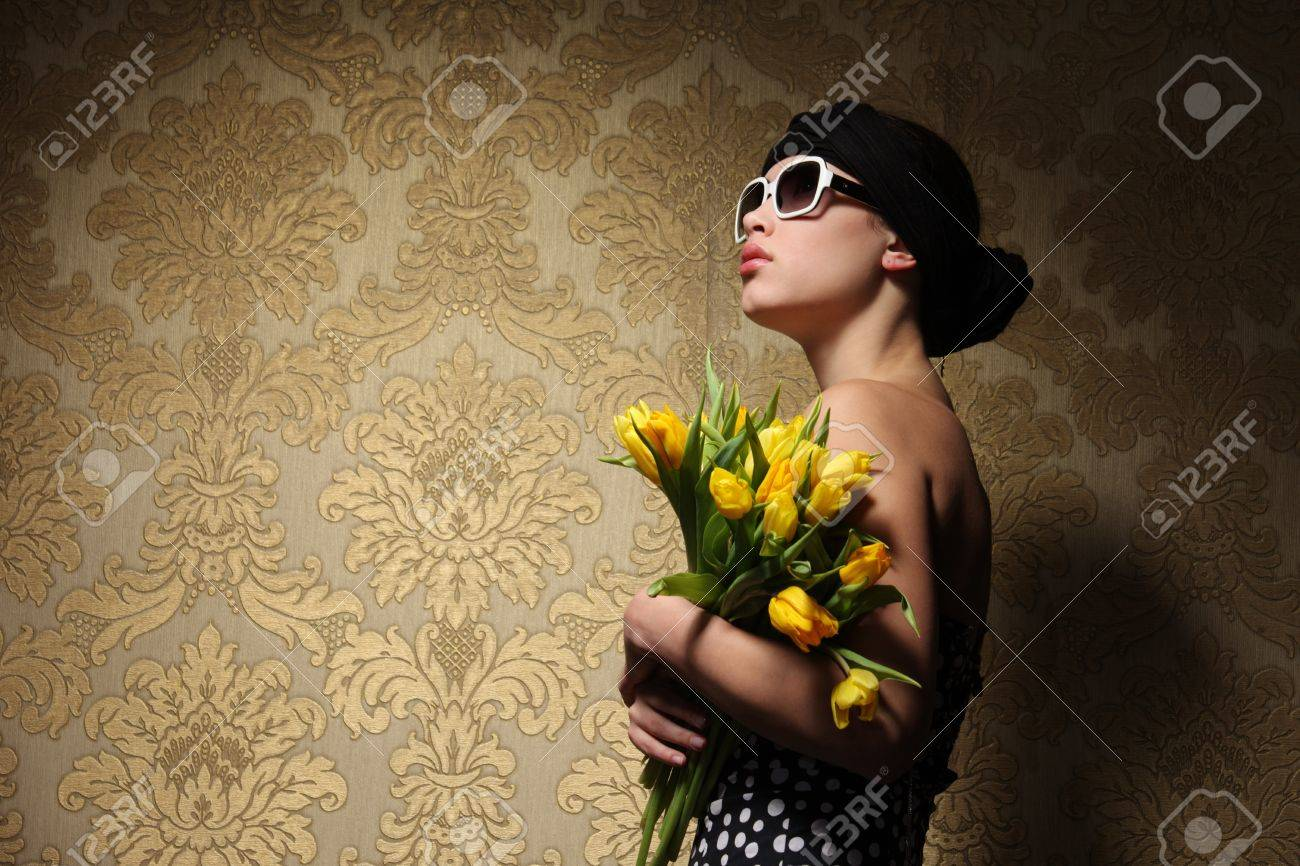 Retro looking young woman in kerchief with yellow flowers looking up against vintage golden wallpaper background. Copyspace. Stock Photo - 8860726