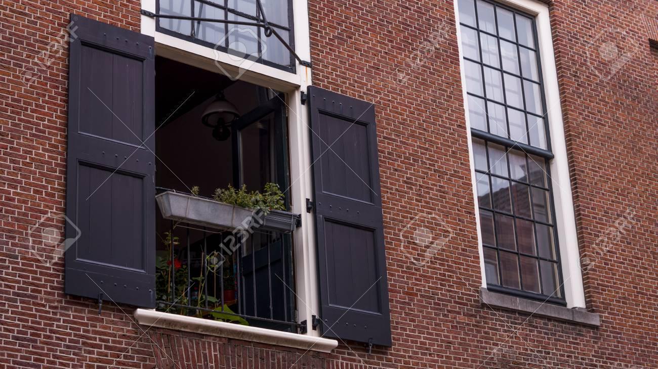 Une Fenêtre Ouverte Avec Des Volets Blancs Ouverts Et Un Rail Noir Avec Un Pot De Plante Suspendu Sur Un Fond De Brique