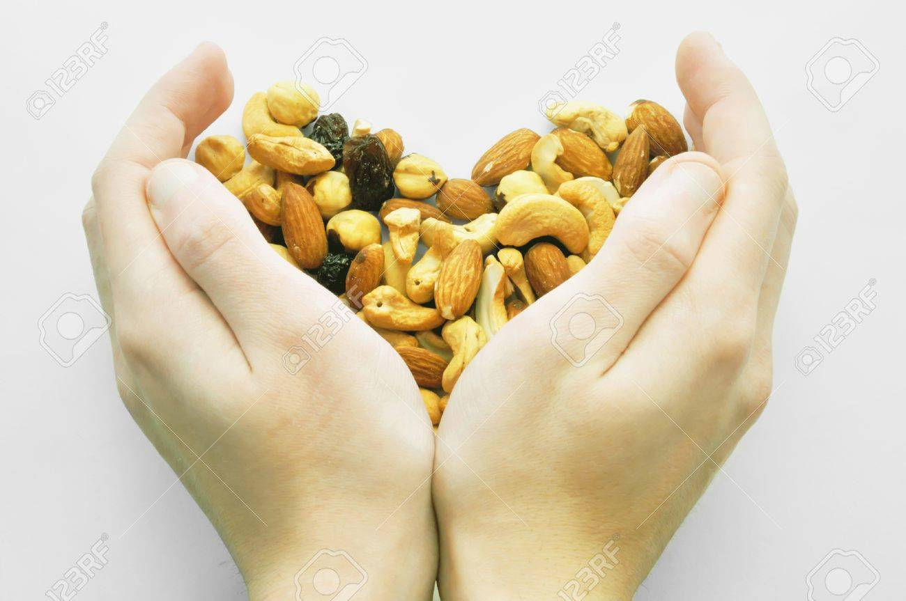 Heart from the dried fruits (nuts), collected with love in hands Stock Photo - 11658416