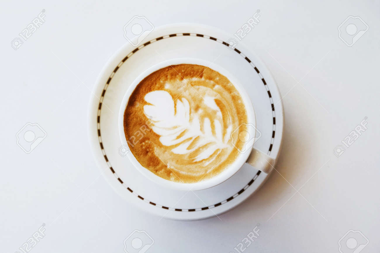 A cup of fresh delicious cappuccino coffee with latte art in the shape of leaf on white background, top view. Space for text. - 154172395
