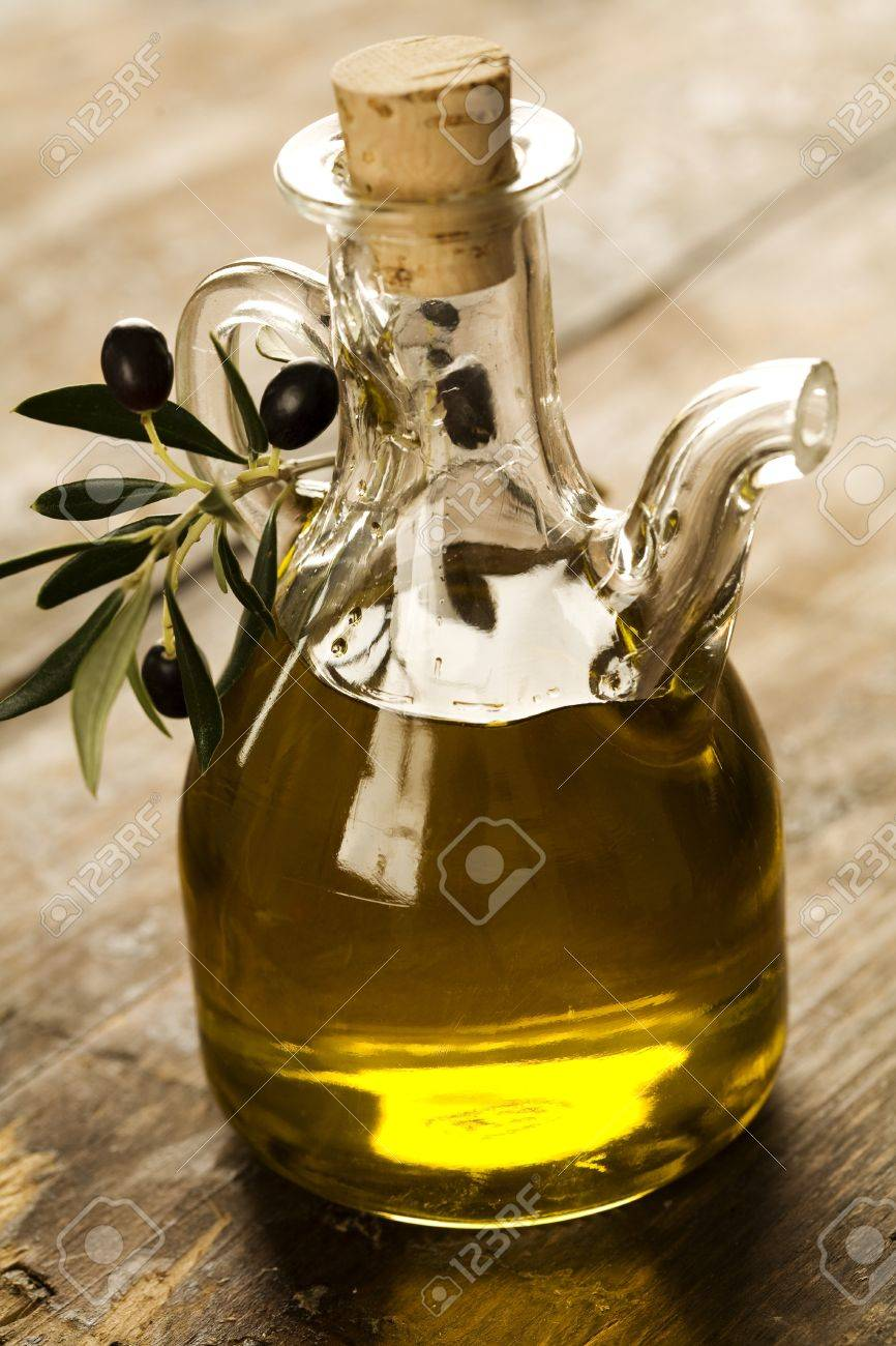 bottle of olive oil on old wooden table and an olive branch Stock Photo - 7769402