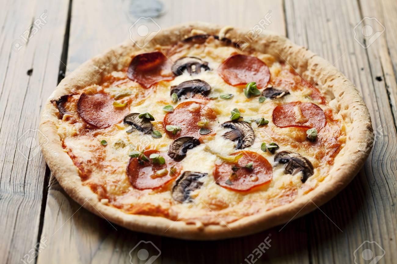 pepperoni and mushrooom pizza on rustic table Stock Photo - 10531209