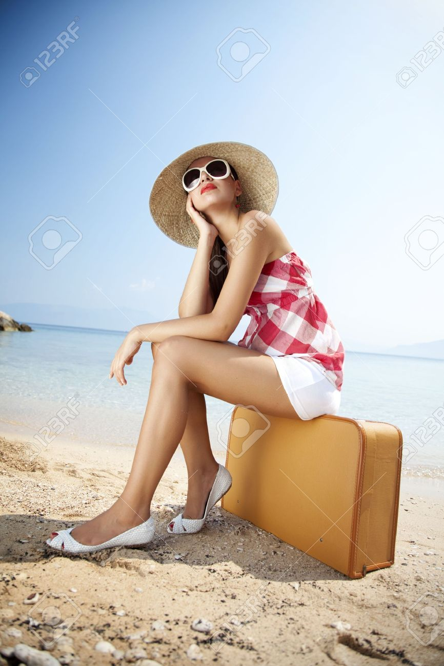 young femaled styled in 50s summer outfit sitting on a retro suitcase on the beach Stock Photo - 10551723