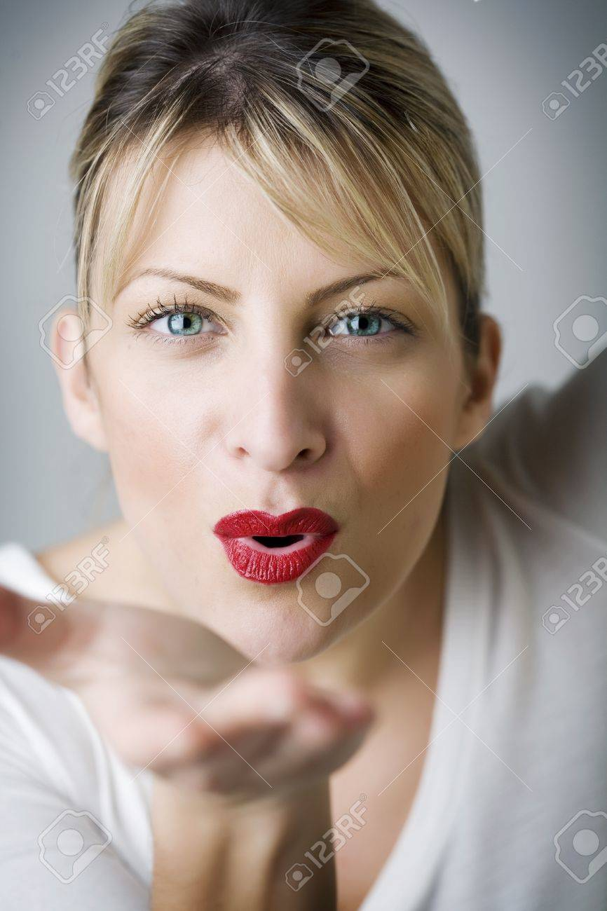 beautiful woman blowing a kiss, skin has been retouched to keep texture Stock Photo - 10721674