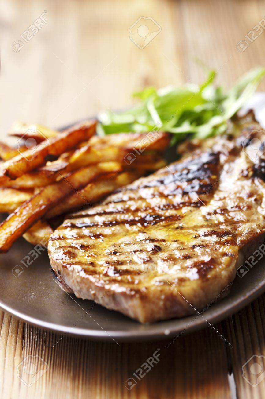 juicy grilled pork chop (neck cut) with greens Stock Photo - 12614731