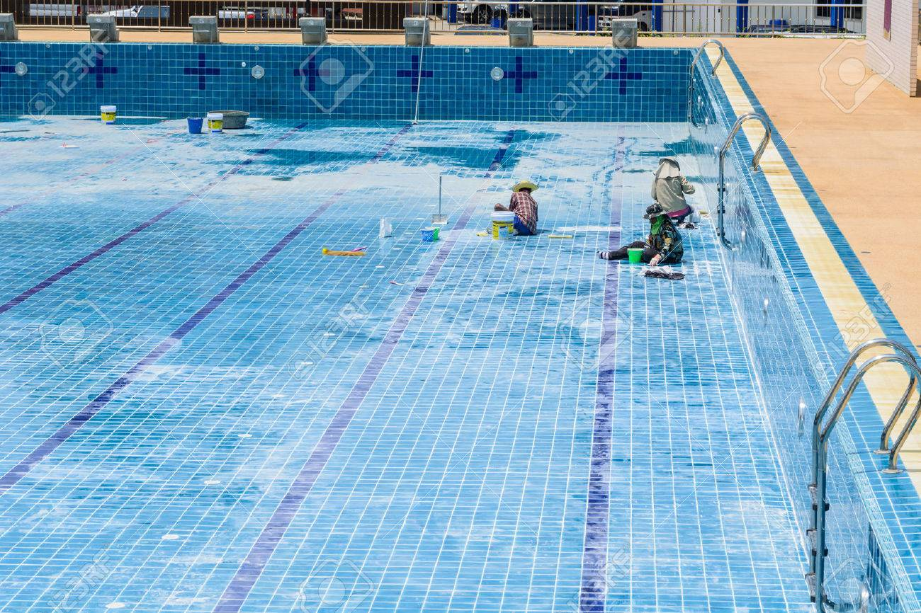 A group of technicians are repairing the damaged pool. - 39387004