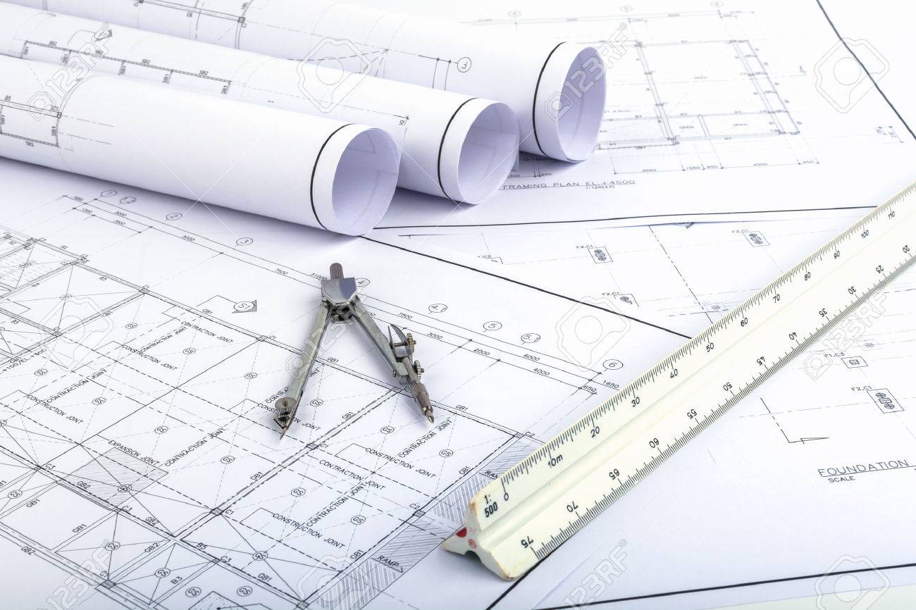 Compasses and Architect scale ruler placed on the desk, filled with building plans. In order to work in a building - 47781213