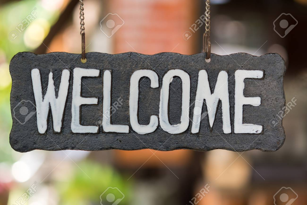Welcome vintage wooden sign on a soft background blur. - 58137120