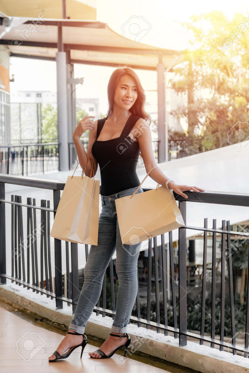 Beautiful young asian woman is carrying shopping bags with shopping bags at standing on the balcony in the outlet, shopping mall. - 170177687