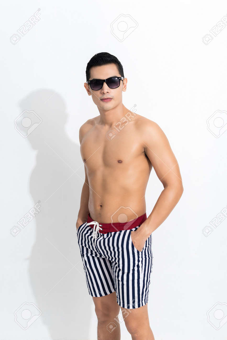 Young muscular guy in striped beach shorts sunbathing wear sunglasses at studio shot isolated on white background. Fashion summer concept. - 170208045