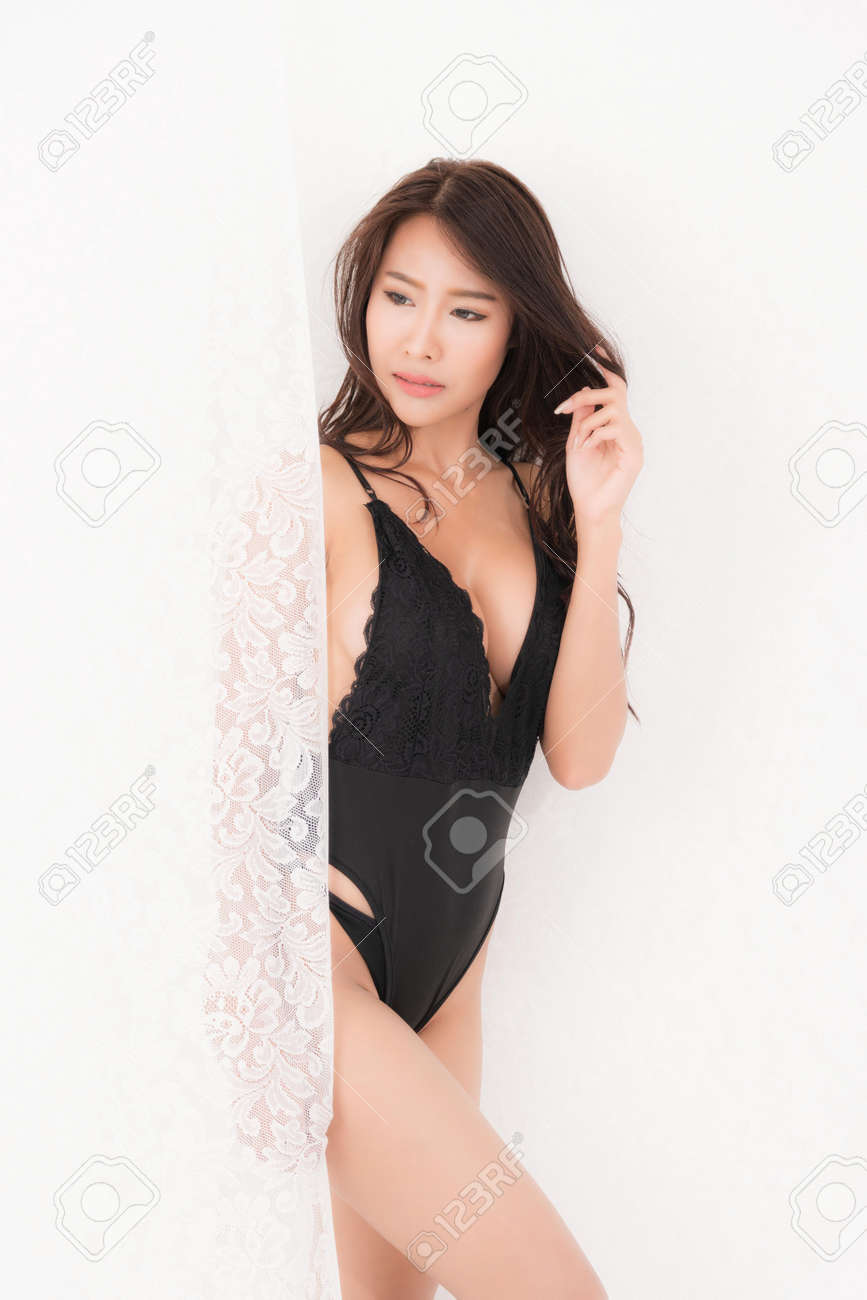 Sexy lifestyle portrait of beautiful alluring young woman brown long haired in black bodysuit stand at white curtains. Concept fashion in bedroom. Studio shot. - 170208056