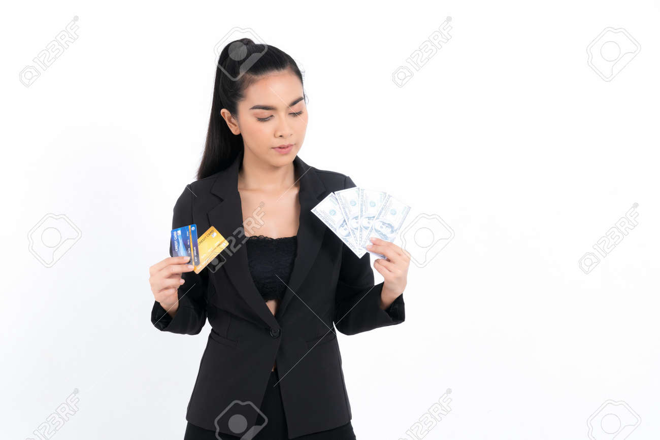 Portrait asian business woman with showing bunch of money banknotes and holding credit card in hand isolated on white background. Concept business and credit. - 170208086
