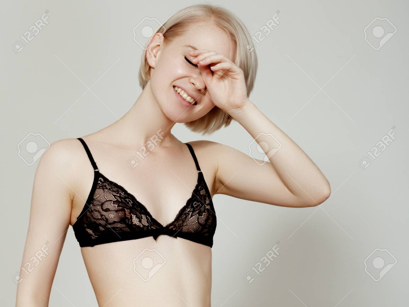 77be7a3cf Stock Photo - Vivacious sexy young blonde woman with a beautiful smile  posing in a black lingerie isolated studio portrait