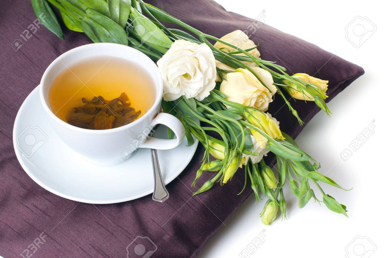cup of green tea and yellow flowers on a brown pillow Stock Photo - 12949268