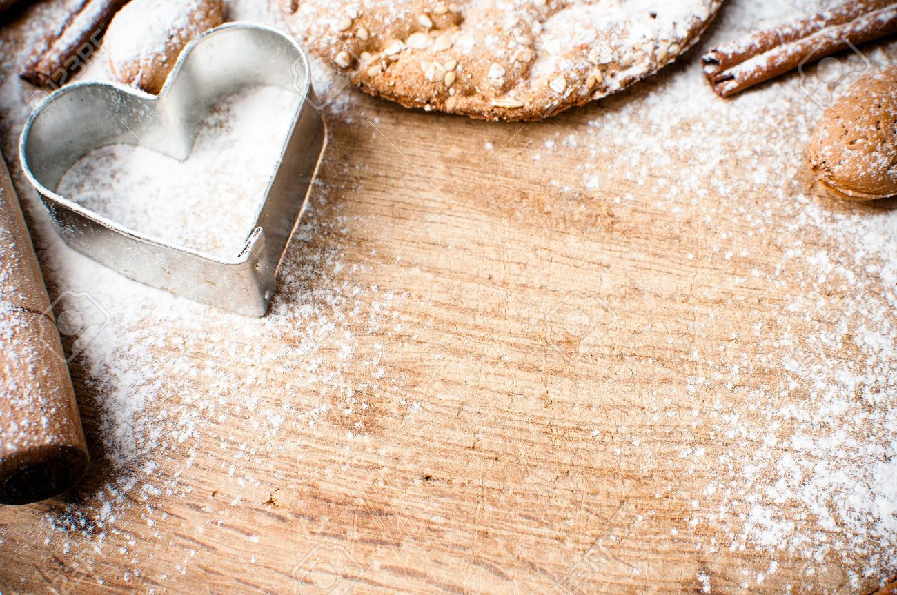 Christmas and holiday baking background, flour, bakeware, heart, cinnamon, cookies and almonds on a wooden board, viewed from above Stock Photo - 16018875
