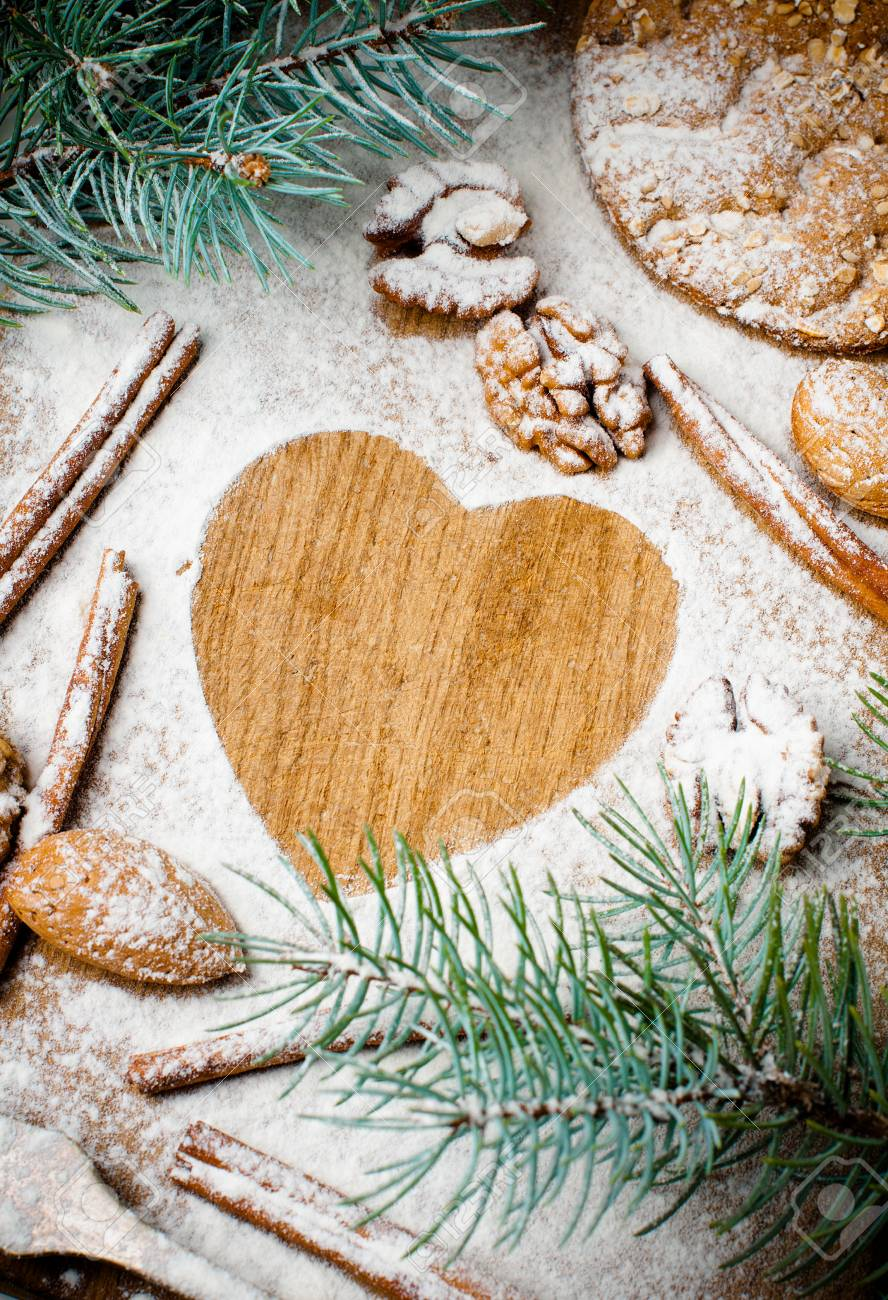 Christmas and holiday baking, cookies, flour, spruce branches and heart-shaped space for text on a wooden board, ready template Stock Photo - 16512588