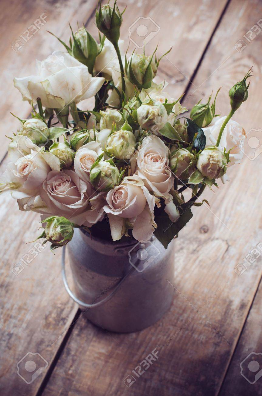 Bouquet of roses in metal pot on the wooden background, vintage style Stock Photo - 21168783