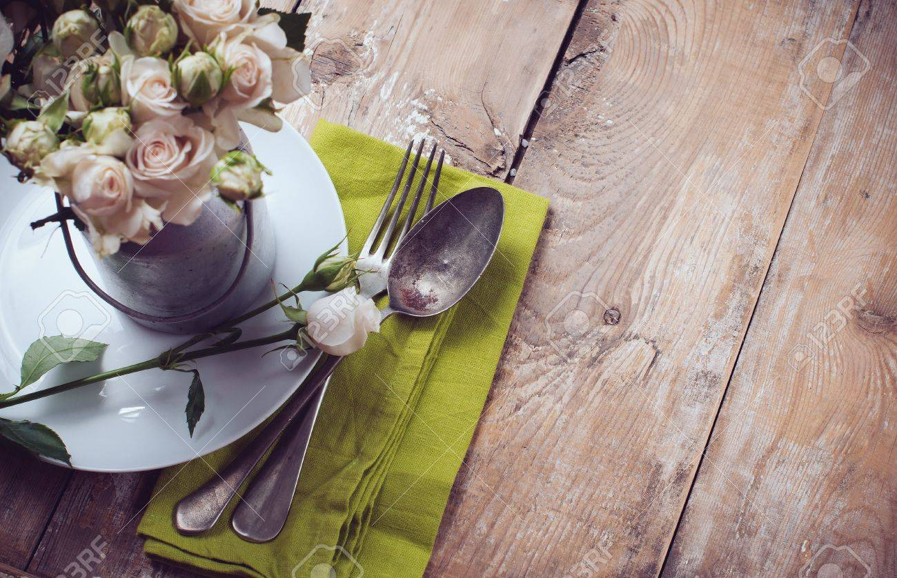 Table Setting Background vintage table setting with rose flowers on a linen napkin on