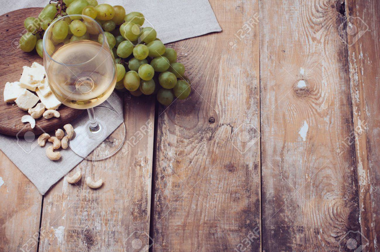 A Glass Of White Wine Grapes Cashew Nuts And Soft Cheese On Wooden