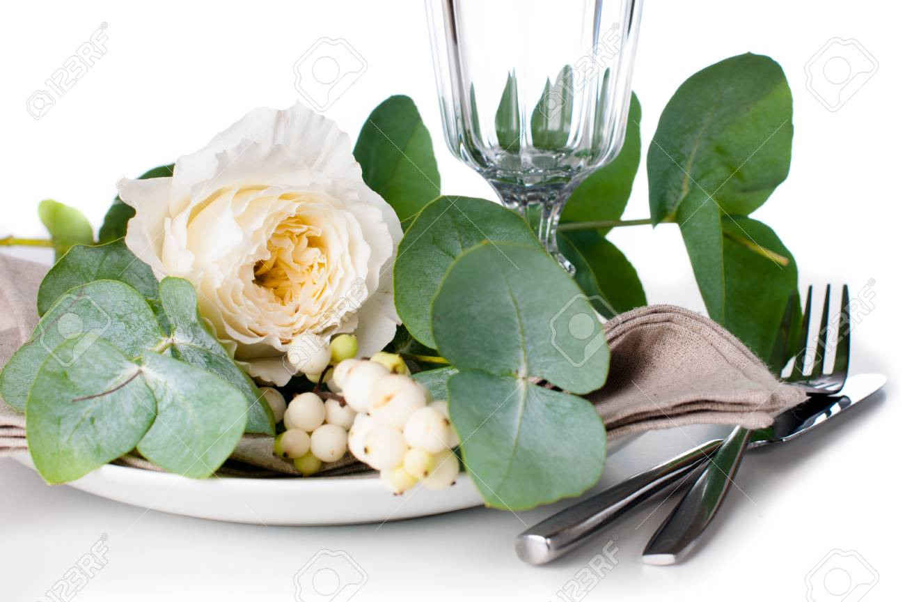 Festive table setting with floral decoration, white roses, leaves and berries on a white background Stock Photo - 22278307