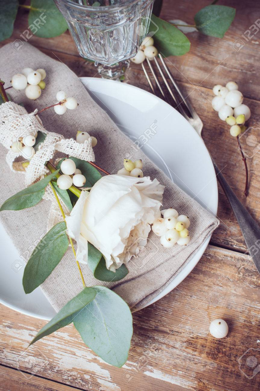 Vintage table setting with floral decorations, napkins, white roses, leaves and berries on a wooden board background Stock Photo - 22278353
