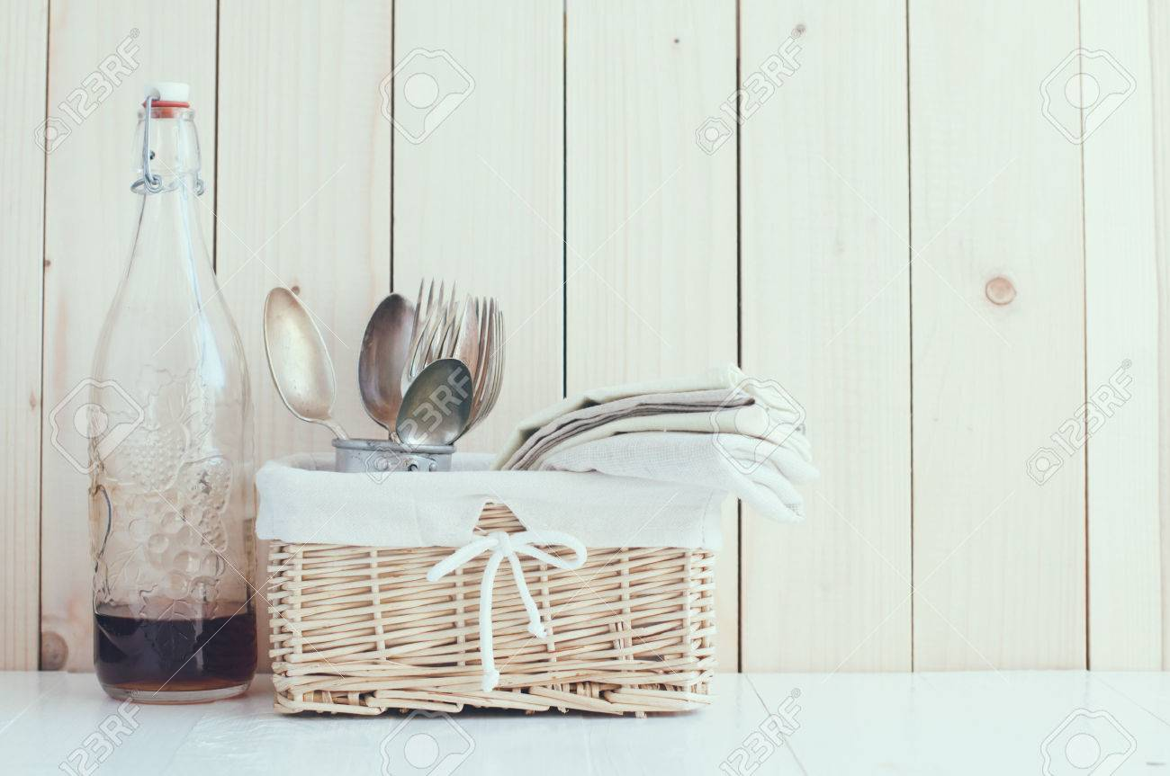 Home Decor Glass Bottle And Wicker Basket And Vintage Cutlery On A Wooden Board Background