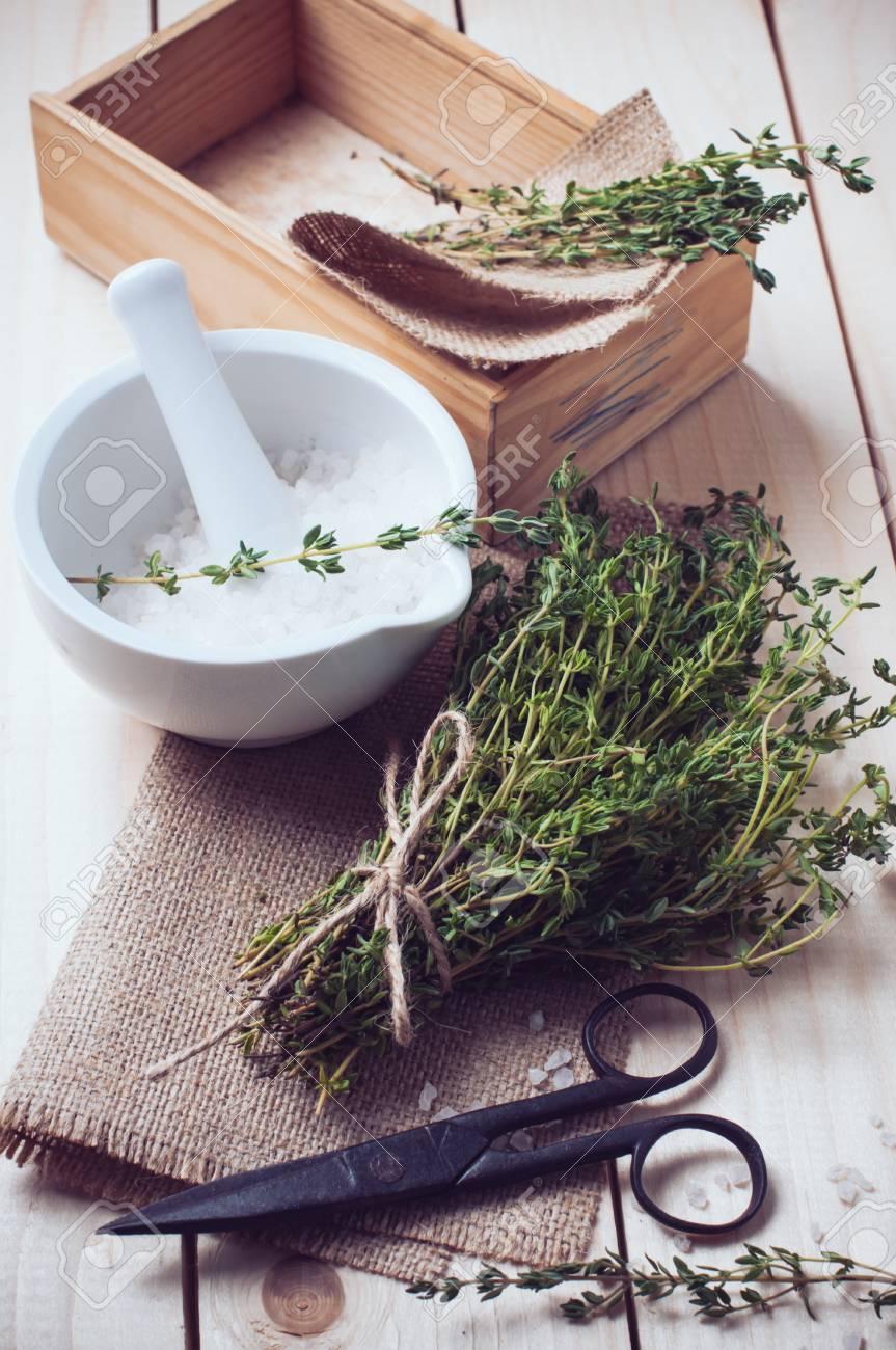 Accogliente cucina rustica casa still life, erbe secche timo, sale in malta  bianca, vecchia scatola di legno e forbici d\'epoca sul tavolo.