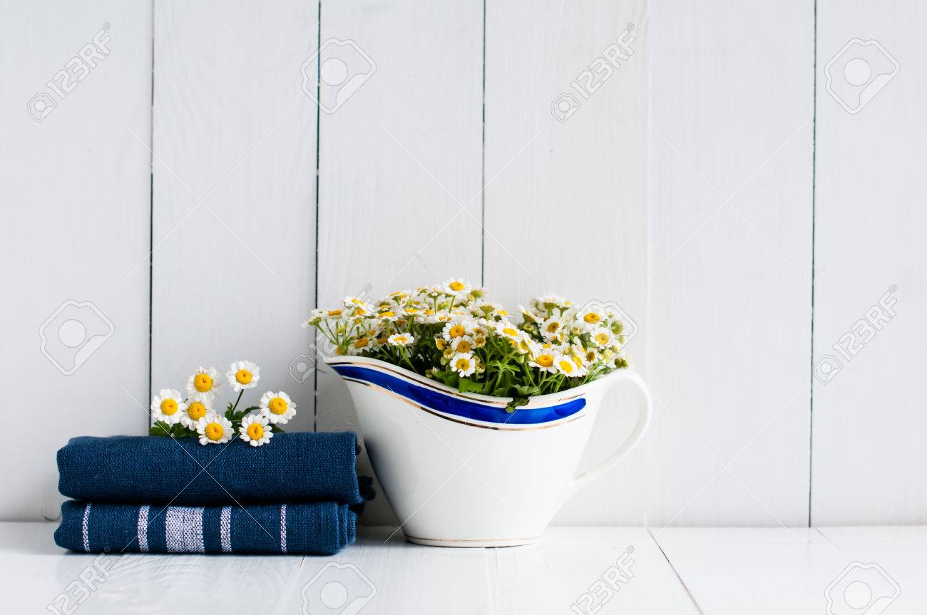 Chamomile flowers in vintage ceramic gravy boat and navy linen.. on