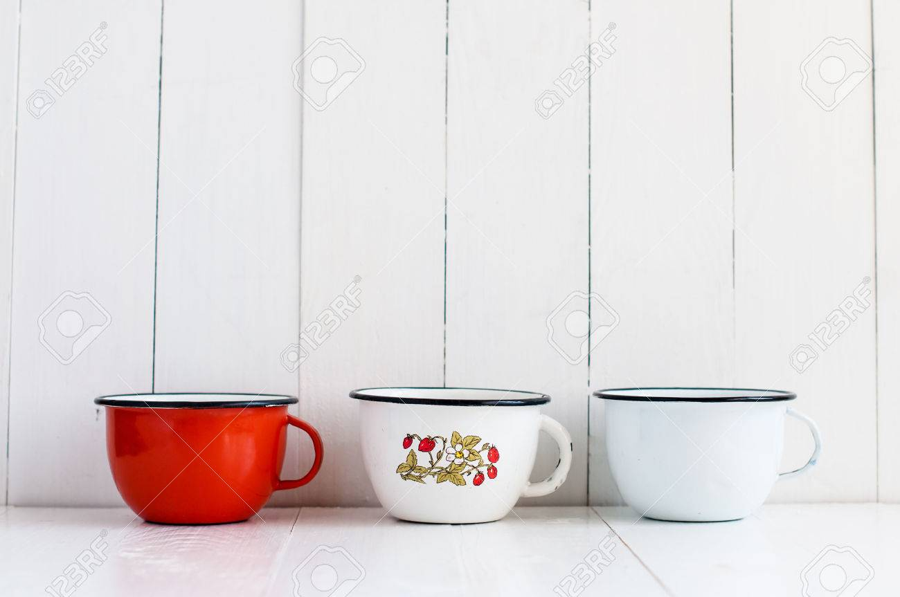 Three Bright Colorful Enameled Mugs On White Painted Wooden Table ...