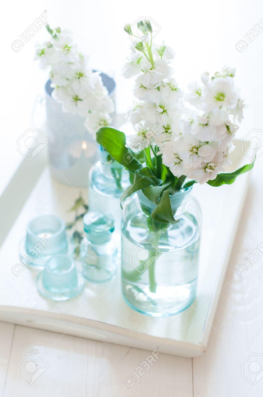 flores blancas en matthiola vendimia botellas de vidrio floreros y velas en una bandeja de madera